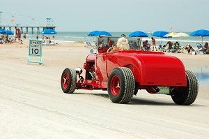 person driving classic car on the beach